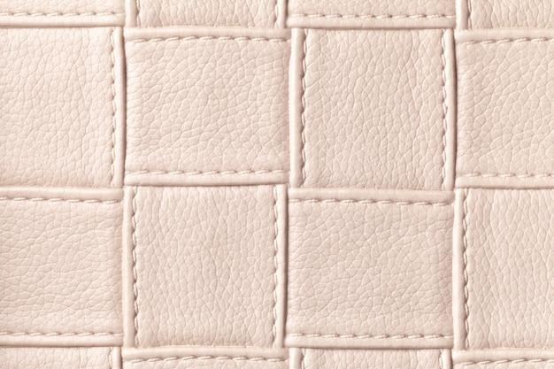 Tekstura tło beżowa skóra z kwadratowym wzorem i ściegiem, makro. abstrakt z nowoczesnej dekoracyjnej jasnobrązowej tkaniny o geometrycznym kształcie.
