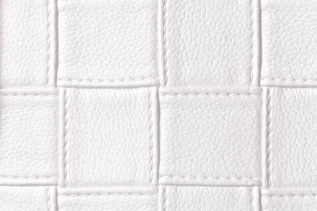 Tekstura tło białej skóry z kwadratowym wzorem i ściegiem, makro. abstrakcja z materiału tekstylnego o geometrycznym kształcie.