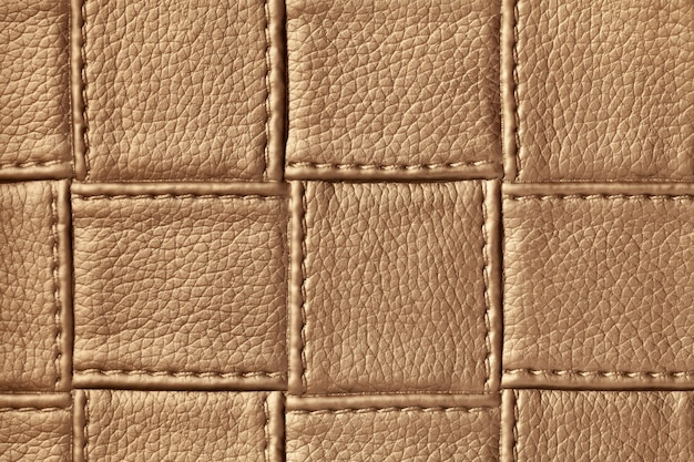 Tekstura tło ciemnobrązowej skóry z kwadratowym wzorem i ściegiem, makro.