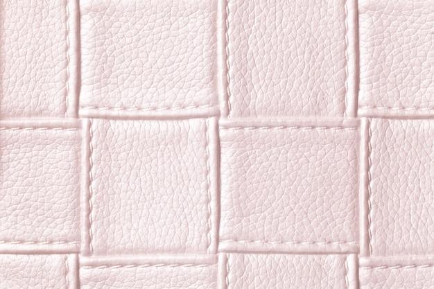 Tekstura tło jasnoróżowej skóry z kwadratowym wzorem i ściegiem