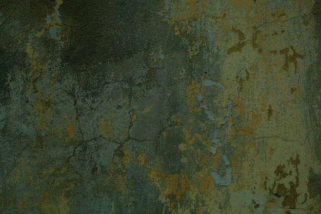 Tekstura tło pęknięty betonowy mur z pozostałościami starej zielonej farby