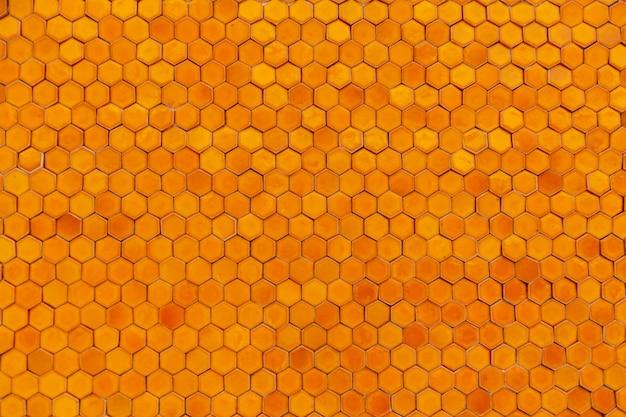Tekstura tło przekroju komórki wosku ula. pomarańczowe geometryczne tło z plastrami miodu