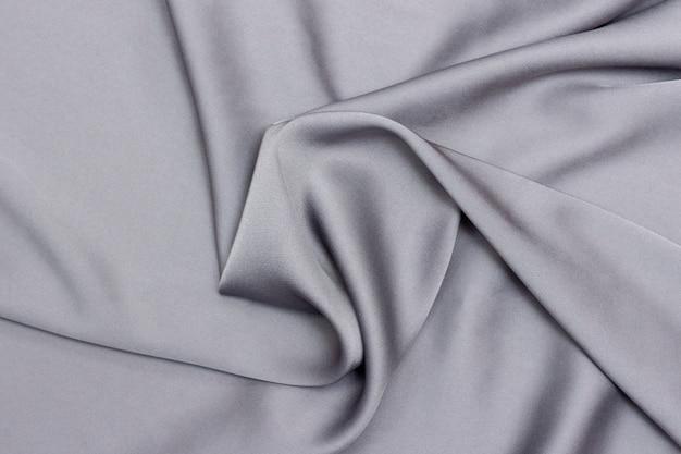 Tekstura tło tkaniny jedwabne, kolor szary. luksusowe tło. gładki elegancki