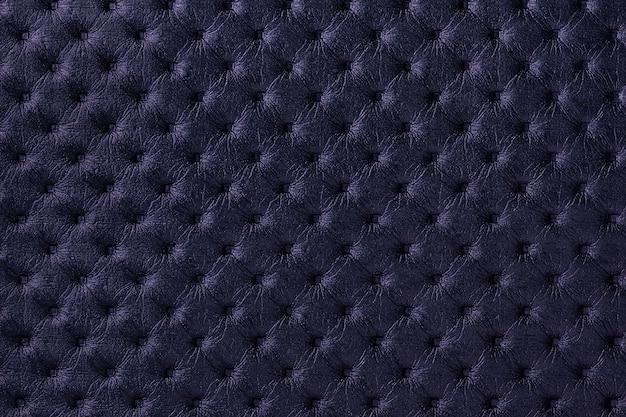 Tekstura tło tkaniny skórzane granatowe z wzorem capitone. ciemnofioletowa tkanina w stylu retro chesterfield.