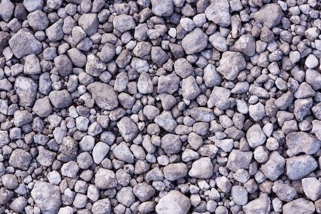 Tekstura tło wielu małych szarych kamieni.