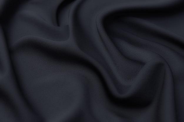 Tekstura, tło, wzór. czarny materiał ze sztucznego jedwabiu do krawiectwa.