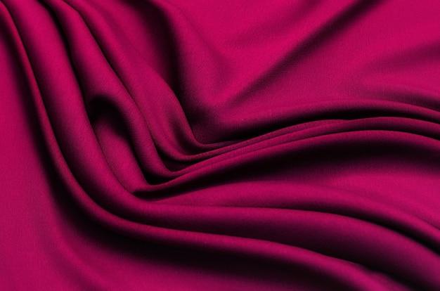 Tekstura, tło, wzór. tekstura czerwonego jedwabiu lub tkaniny bawełnianej lub wełnianej. piękny wzór tkaniny.