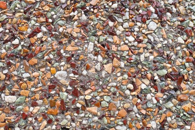 Tekstura. wielobarwne kamienie gruzowe na betonowej podstawie.