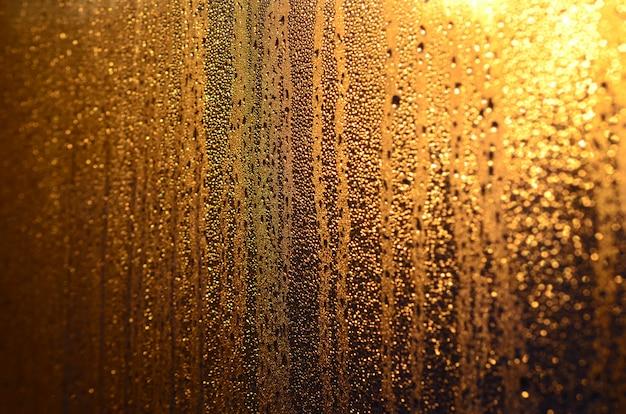 Tekstura zamglonego szkła z dużą ilością kropli i kroplami kondensacji na słońcu o świcie. zdjęcie w tle