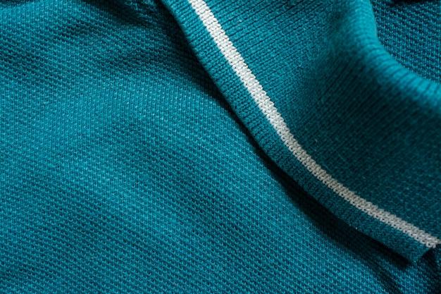 Tekstura zielonej koszulki polo, tkanina bawełniana.