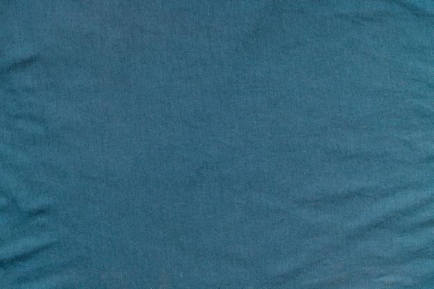 Tekstura zmiętej zielonkawej tkaniny.