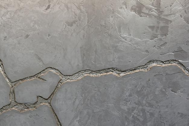 Teksturę szarej betonowej ściany zdobi głębokie pęknięcie w kolorze srebrnym.