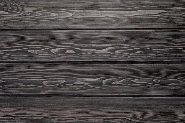 Teksturowana powierzchnia drewna. naturalne tło z desek modrzewiowych. ciemny kolor.