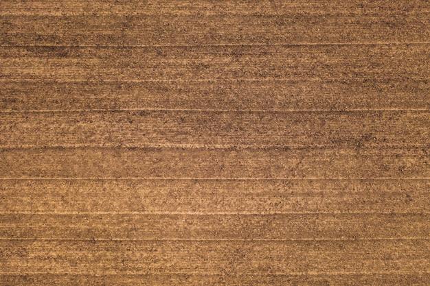 Teksturowana powierzchnia ziemi z równoległymi liniami od kultywatora, widok z góry w tle. żyzna gleba. koncepcja rolnictwa