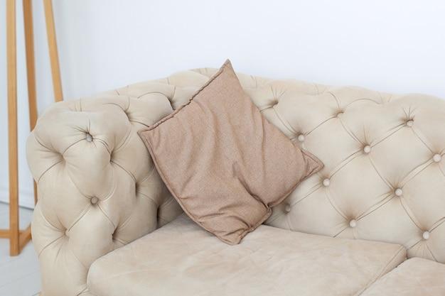 Teksturowane sofy wewnętrzne i neutralne kolory. poduszka na kanapie w pokoju. brązowa poduszka na stylowej kanapie w salonie. wystrój domu, szczegóły wnętrza. dom w stylu skandynawskim. projekt pokoju