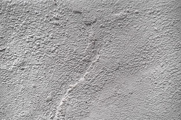 Teksturowane tło sztukaterie ściennej z zadrapaniami, zadrapaniami i plamami. nierówne tło tynku w kolorze białym i szarym na miejsce na kopię
