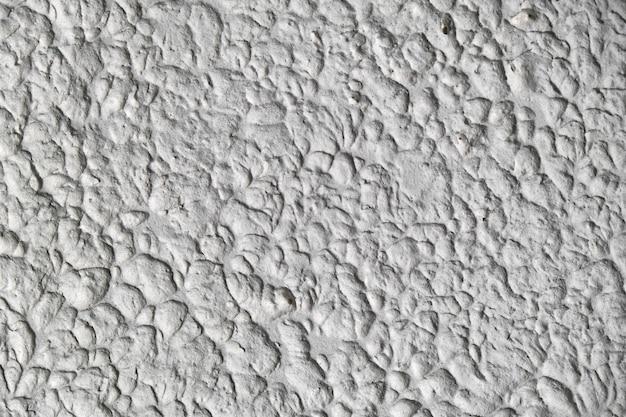 Teksturowane tło sztukaterie z zadrapaniami, zadrapaniami i plamami. nierówne tło tynku w kolorze białym i szarym na miejsce na kopię