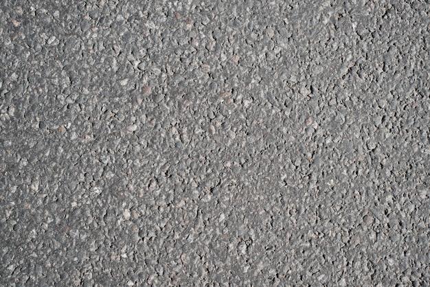 Teksturowane tło z szarego asfaltu, widok z góry. duże granulki i kamienie, konstrukcja drogi, tło z miejscem na kopię