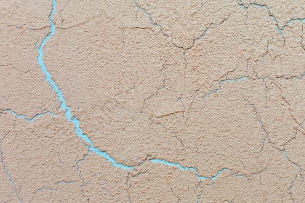 Teksturowane tło żółty gliny pęknięty tynk. tło ściany.