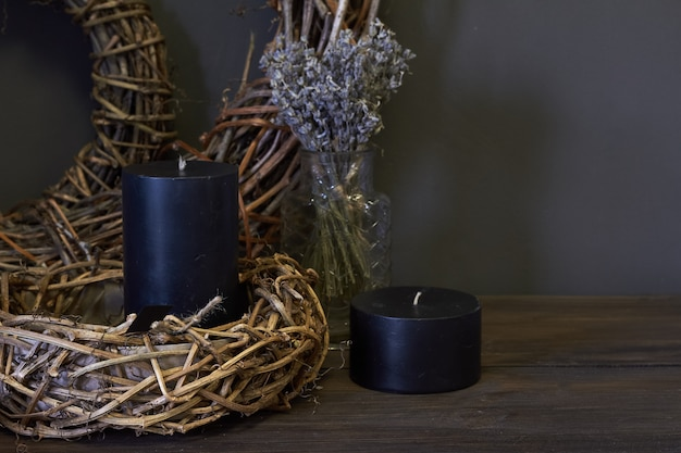 Teksturowany wieniec bożonarodzeniowy wykonany z tkaninowych gałęzi winorośli, czarnych świec i suchej lawendy w szklanym wazonie, selektywna ostrość
