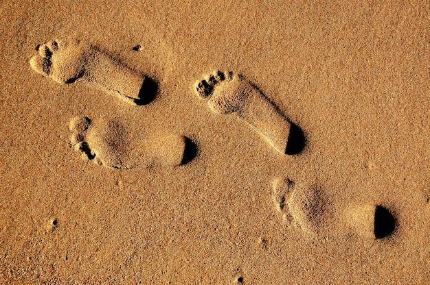 Tekstury tła odciski stopy ludzcy cieki na piasku blisko wody na plaży.