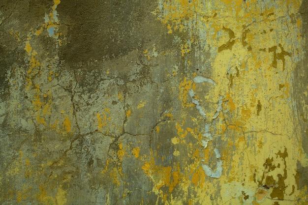 Tekstury tła popękanego muru betonowego z pozostałościami starej zielonej farby w widoku pełnej klatki.