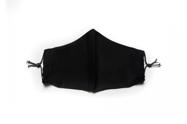Tekstylna maska na twarz czarna na białym tle na białym tle. ochrona dróg oddechowych przed infekcją koronawirusem. sprzęt ochrony osobistej.