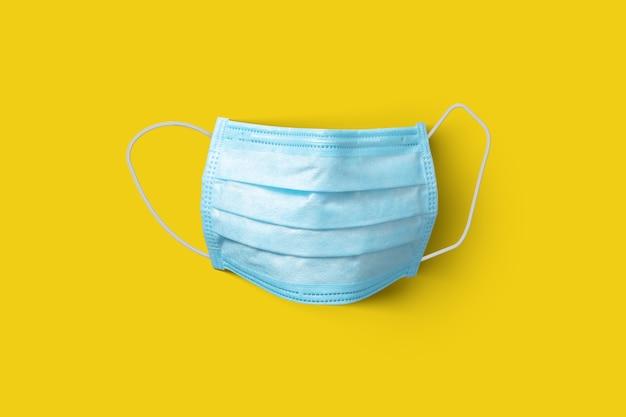 Tekstylna medyczna antybakteryjna ochronna niebieska maska na żółtą ścianę, miejsce na kopię. koncepcja profilaktyki chorób układu oddechowego i wirusów.