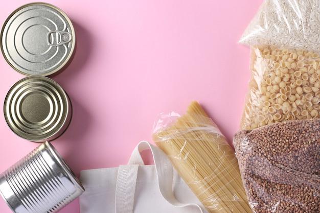 Tekstylna torba spożywcza z zapasami żywności kryzysowej na różowej powierzchni. ryż, kasza gryczana, makaron, konserwy. darowizna żywności