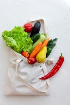Tekstylna torba wypełniająca z warzywami i owoc, odgórny widok na bielu.