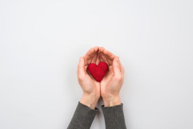 Tekstylne czerwone serce w ręce kobiety na pastelowym tle
