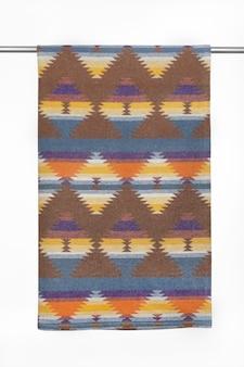 Tekstylne tło z geometrycznym wzorem z wełnianego koca z bliska na białym tle