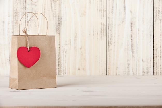 Tekturowa torba prezentowa z metką w kształcie serca na drewnianym tle