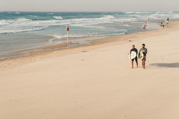 Tel awiw, izrael - 3 listopada 2018: dwóch młodych surferów z deskami surfingowymi spacery piaszczystą plażą morza śródziemnego.