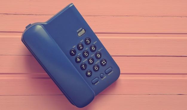 Telefon biurowy na różowym drewnianym stole