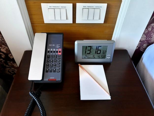 Telefon cyfrowy zegar i papierowa notatka z ołówkiem na biurku w pokoju hotelowym
