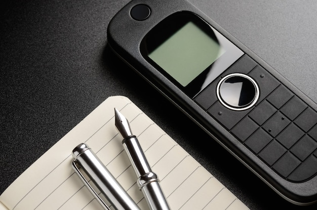 Telefon, długopis, notatnik. skontaktuj się z nami koncepcja