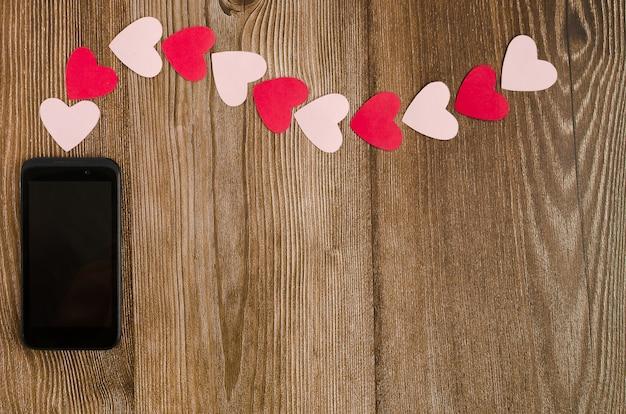 Telefon emitujący sygnał w kształcie serc na drewnianym stole.