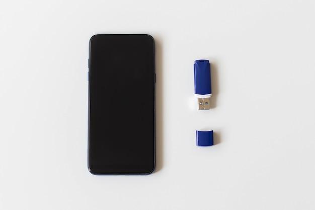 Telefon i pendrive na białej powierzchni