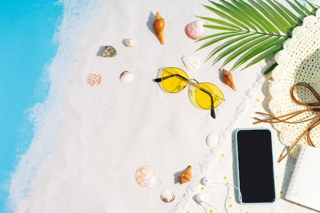 Telefon jest umieszczony na piasku, otoczony muszelkami i okularami przeciwsłonecznymi