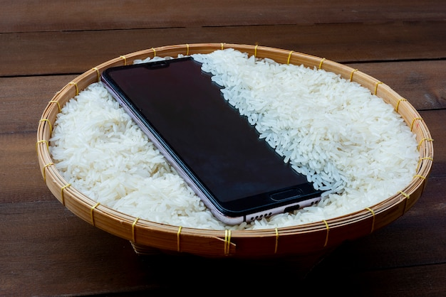 Telefon jest w rowku ryżu. pozwól wilgoci wniknąć w ziarno
