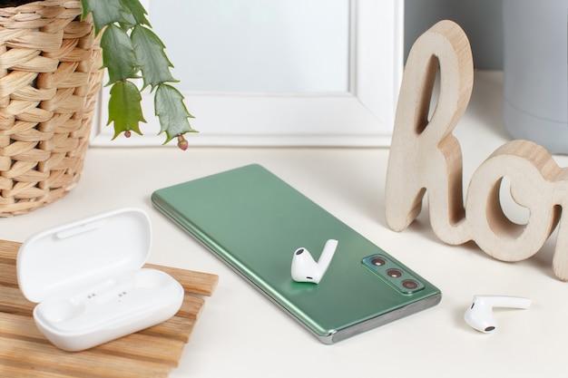 Telefon komórkowy, bezprzewodowe słuchawki i roślina na stole z bliska