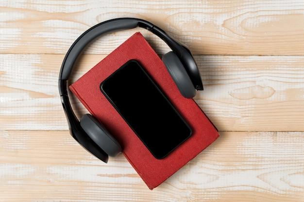 Telefon komórkowy, headphonesi i książka na drewnianym tle. koncepcja audiobooka. widok z góry