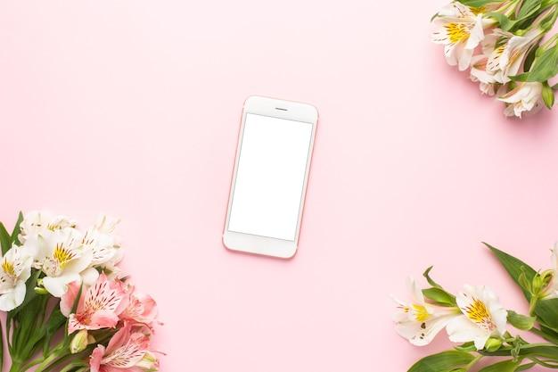 Telefon komórkowy i białe kwiaty alstroemeria na różowo