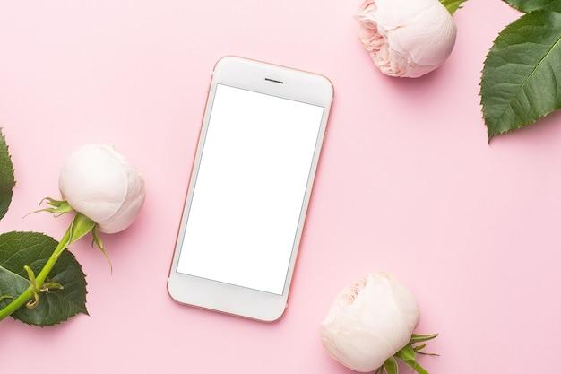 Telefon komórkowy i białe róże na pastelowym różowym tle z copyspace. przedmiot na wakacje i miłość
