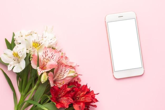 Telefon komórkowy i biało-różowy kwiat alstroemeria na różowo