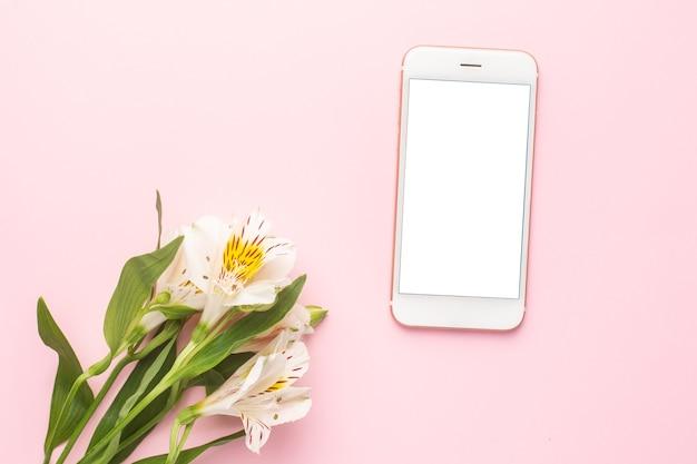 Telefon komórkowy i biały kwiat alstroemeria na różowo
