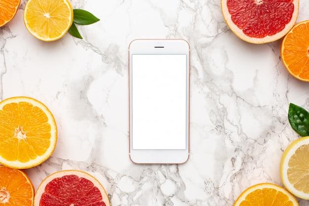 Telefon komórkowy i cytrusy na marmurowej powierzchni, płaska owocowa, minimalna letnia kompozycja z grejpfruta, cytryny, mandarynki i pomarańczy