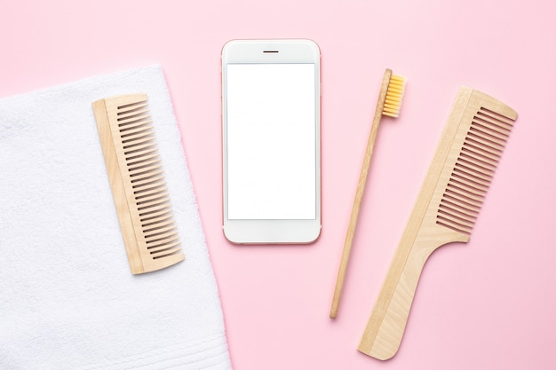 Telefon komórkowy i ekologiczna drewniana szczoteczka do zębów, grzebień, szczoteczka do masażu na sucho na różowo