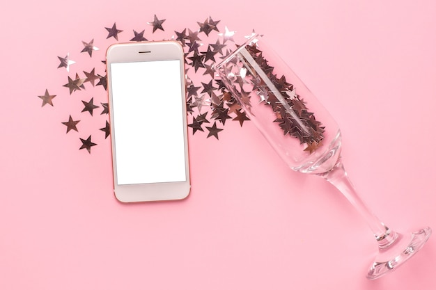 Telefon komórkowy i kieliszek do szampana ze srebrnymi gwiazdkami